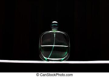 Close-up of perfume bottle on black background.