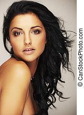 Close-up portrait of a beautiful brunett model in studio on light background