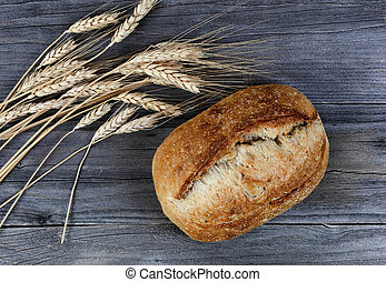 Close up view of homemade sourdough bread with dried wheat stalks on age wood