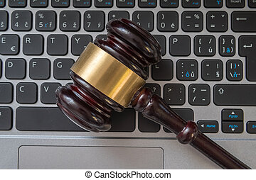 Close up view on gavel and computer keyboard. Internet security
