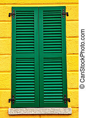 Closed green window shutters on yellow house facade.