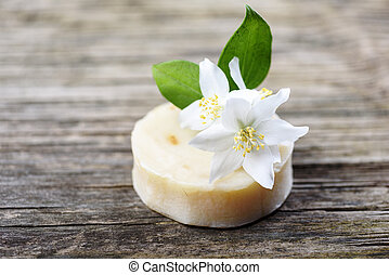 Closeup of organic handmade natural soap with goat milk and jasmine flower herbs on vintage wooden table. Skincare cosmetics.
