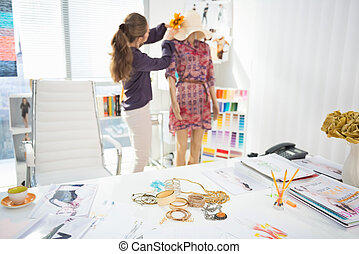 Closeup on accessories on table and fashion designer decorating garment in background