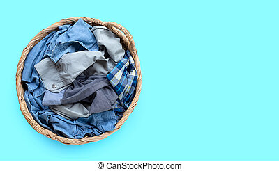 Clothes in laundry basket on blue background.