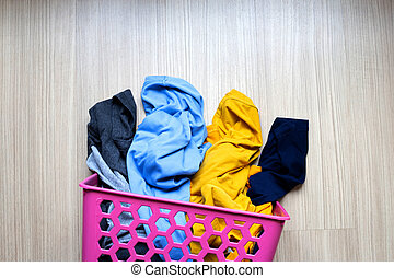 Clothes in pink plastic laundry basket.