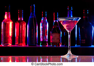 Cocktail glass with drink in the bar with bottles in the dark background