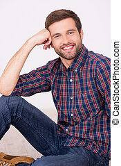Confident handsome. Handsome young man smiling and leaning his head on hand while sitting on the floor