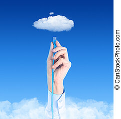 Hand with the cable connected to the cloud. Conceptual image on cloud computing theme.