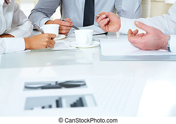Close-up of businesspeople discussing plan at meeting