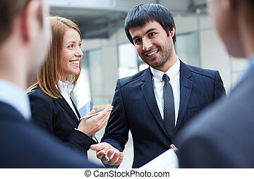 Group of business partners interacting at meeting, focus on smart man and business lady