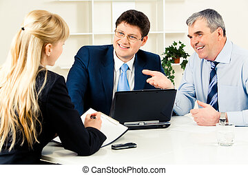 Three business partners discussing new working ideas around table with laptop on it