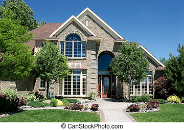 a modern, newly built, american home. very clean image, shot against a blue sky.