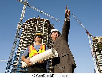 Contractor and foreman at the job site with hirise construction in the background