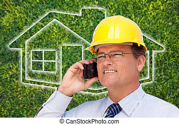 Contractor in Hardhat on Cell Phone Over House Icon and Grass
