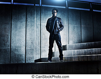 cool urban african american man on distopic concrete steps
