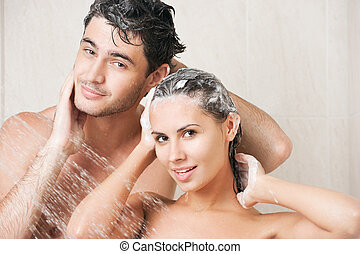 Young couple washing their heads in the shower