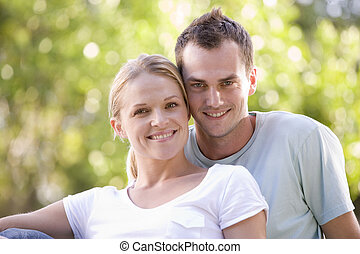 Couple sitting outdoors smiling