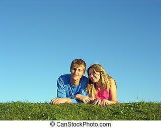 couples lie on grass