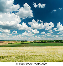 deep blue sky with clouds and green landscape