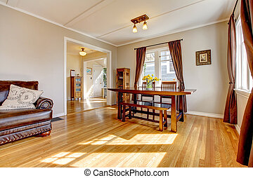 Dining room with brown curtain and hardwood floor and leather sofa.
