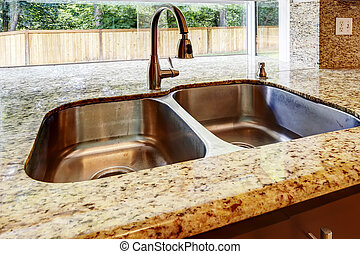 Kitchen cabinet with double steel sink and granite counter top. Close up view