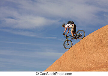 A fearless mountain biker drops down a steep section of Moab's slickrock trail.
