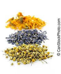 Piles of dried medicinal herbs camomile, lavender, calendula on white background
