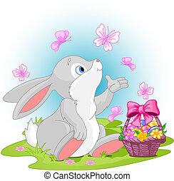 A cute Easter bunny sitting near Easter eggs basket.