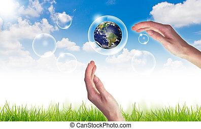 Eco concept : Hand hold globe in bubbles against the sun and the blue sky