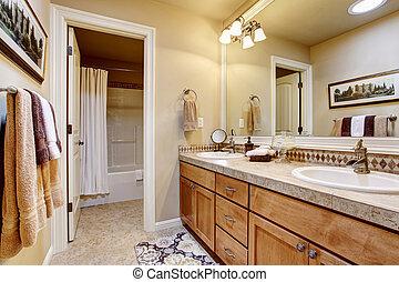 Elegant bathroom interior with large mirror, granite counter top and tile floor.