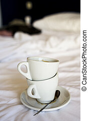 empty cups of coffee on an unmade bed