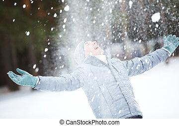 Portrait of cute guy taking pleasure on snowy winter day