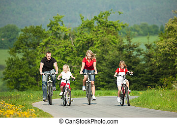 Family with children having a weekend excursion on their bikes on a summer day