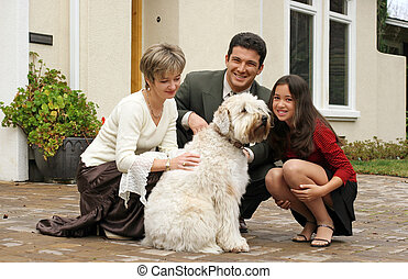 Happy family with a dog in front of the home