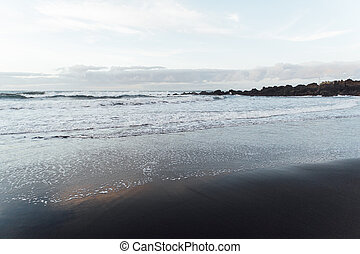 Fantastically beautiful sunset on the north coast of Tenerife, a beach with stones and black sand.