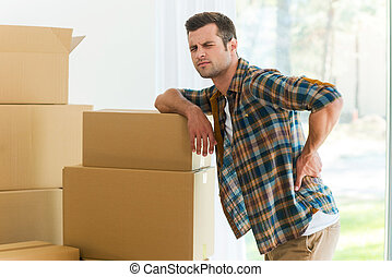 Feeling pain in back. Frustrated young man holding hand on his back and expressing negativity while leaning at the cardboard box