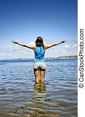 Beautiful woman in the water feeling the breeze