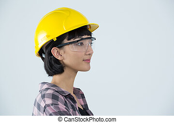 Female architect wearing hard hat and safety glasses against white background
