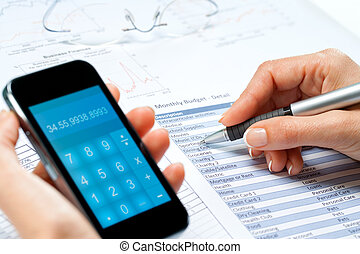 female hands calculating budget with smart phone.