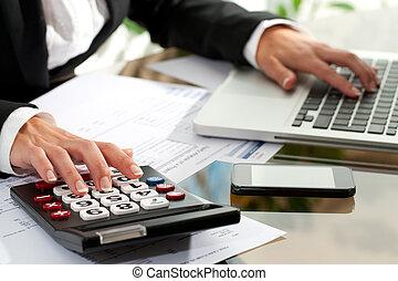 Female hands working on calculator.