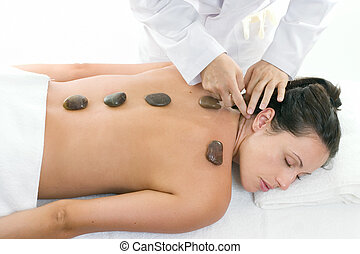 A female receiving massage and hot rock treatment to back and neck at a beauty salon or day spa facility.