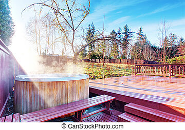 Fenced backyard area with hot tub and walkout deck