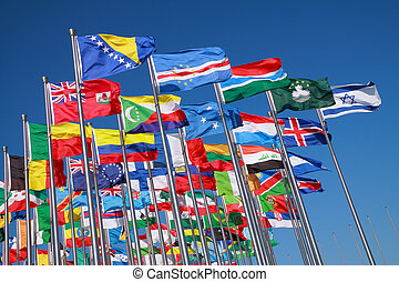 Flags of all nations of the world are flying in blue sunny sky