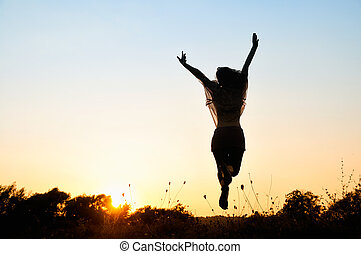 Silhouette of a beautiful girl jumping over sunset, unrecognizable person