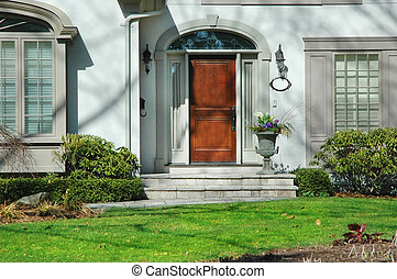 Front entrance of home with flower urn and wood door