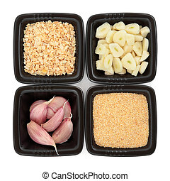 Garlic cloves whole and chopped, flakes and salt in black square dishes over white background.