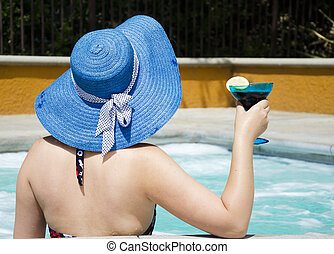 Girl in summer hat in jacuzzi (hot tub)