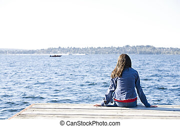 Girl sitting alone on dock by lake, looking out over water.