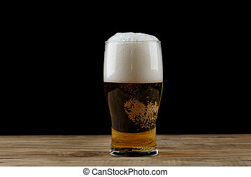 Glass of light beer with foam on a wooden table.