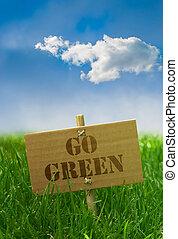 Go green text written onto a carton board grass blue sky